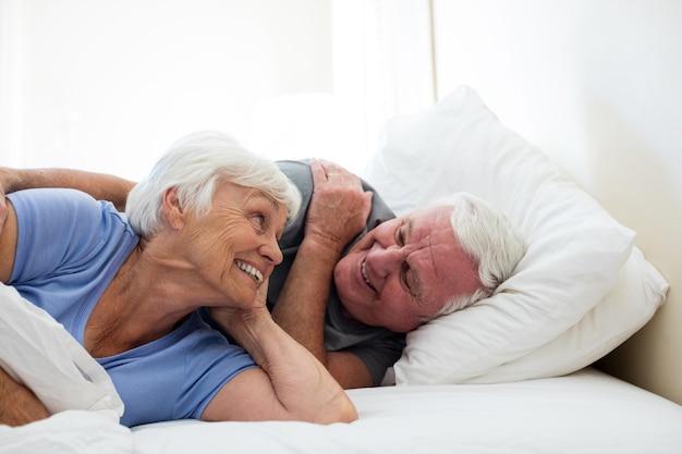 自宅の寝室でリラックスした年配のカップル