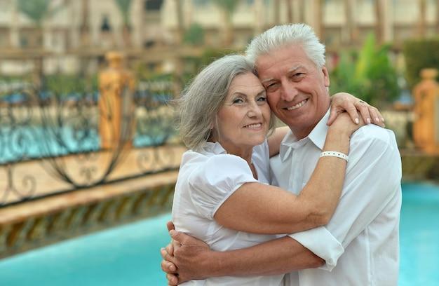 ホテルリゾートのプールの近くでリラックスする年配のカップル