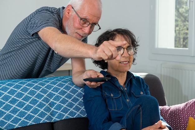 ソファでリラックスして自宅でテレビを見ている年配のカップル
