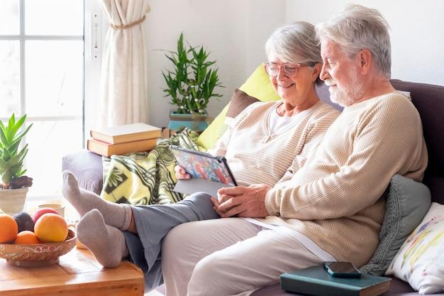 집에서 소파에 앉아 디지털 태블릿을 보고 웃고 있는 노부부
