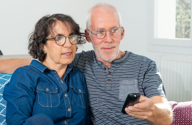 Senior couple relaxing on sofa and watching tv at home