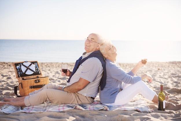ビーチでワインのボトルでリラックスする年配のカップル