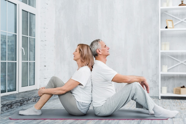 Senior couple resting after exercise in living room