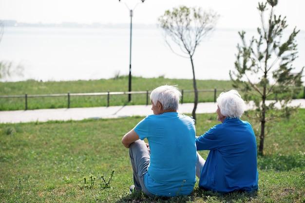 Senior couple resting on lawn
