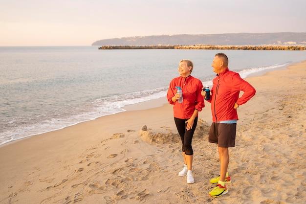 ビーチでジョギングしながら休んでいる年配のカップル