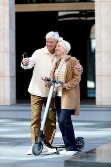 Пожилая пара катается на электросамокате в городе и делает селфи