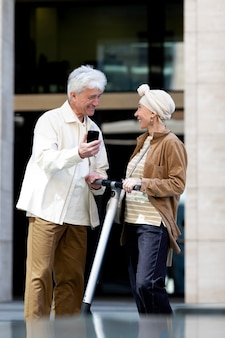 Senior couple riding an electric scooter in the city and using smartphone