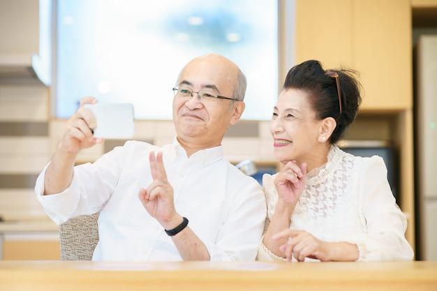 屋内でスマートフォンで撮影する年配のカップル