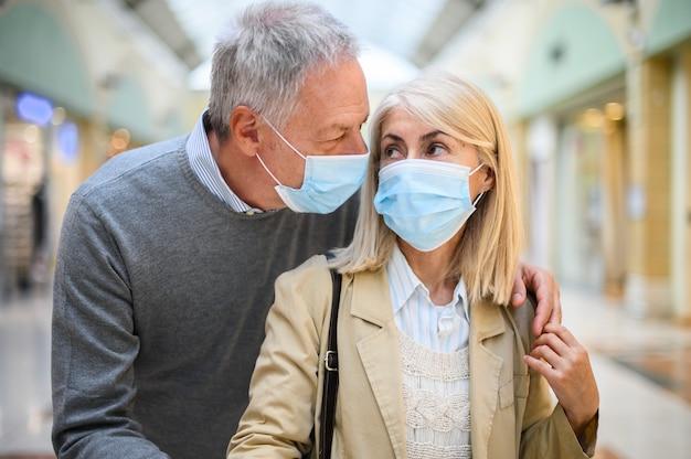 Пожилая пара делает покупки в торговом центре во времена коронавируса, в масках