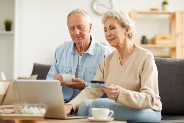 Пожилая пара, делающая покупки онлайн