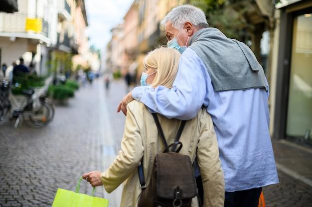 Пожилая пара делает покупки на открытом воздухе во времена коронавируса, в масках