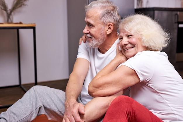 一緒にスポーツ運動をした後、年配のカップルが床で休んで座って、健康でスポーティーであることを楽しんで、笑顔を抱き締めます