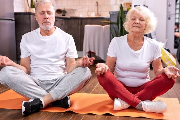 年配のカップルは、蓮華座で瞑想し、ヨガに従事し、目を閉じて落ち着いて床に座ります