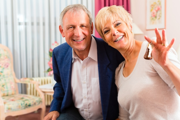 Senior couple sitting on bed in hotel room