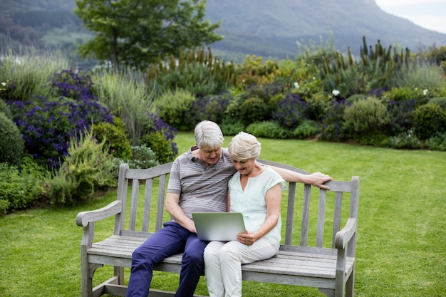 Senior couple sitting on bench and using laptop