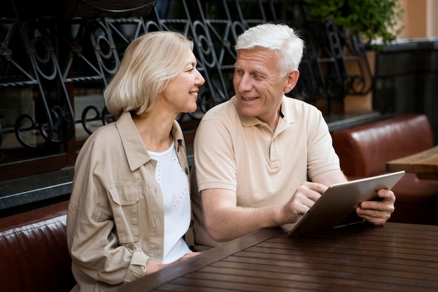 Senior couple sitting down while out in the city with tablet