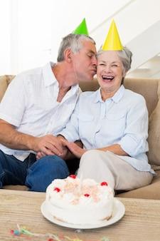 Старший пара, сидя на диване, отмечая день рождения