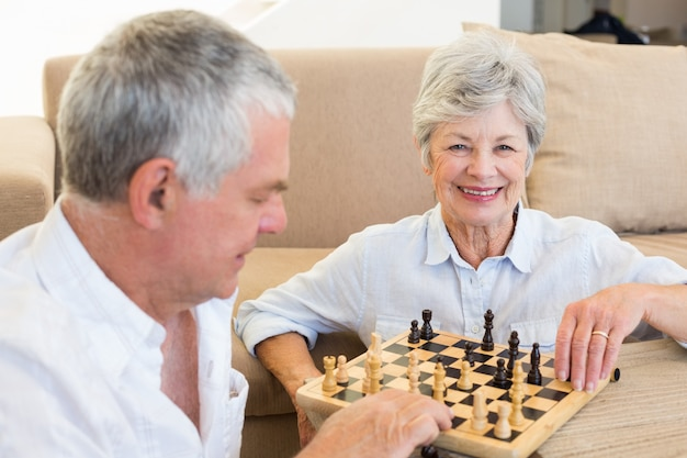 チェスをする床に座っているシニアカップル