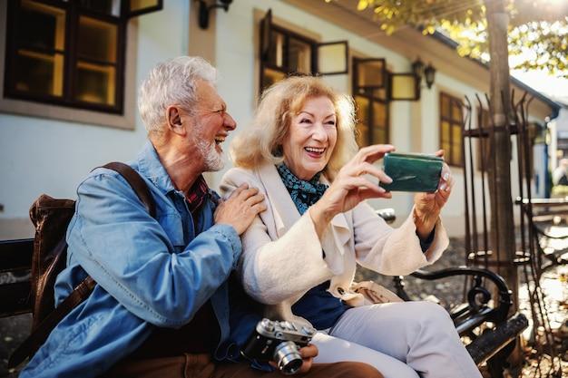 Старшие пары сидят на скамейке в центре города и смеются и делают селфи.