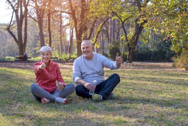 Пожилая пара счастливо сидит на траве в парке, подняв пальцы вверх при дневном свете
