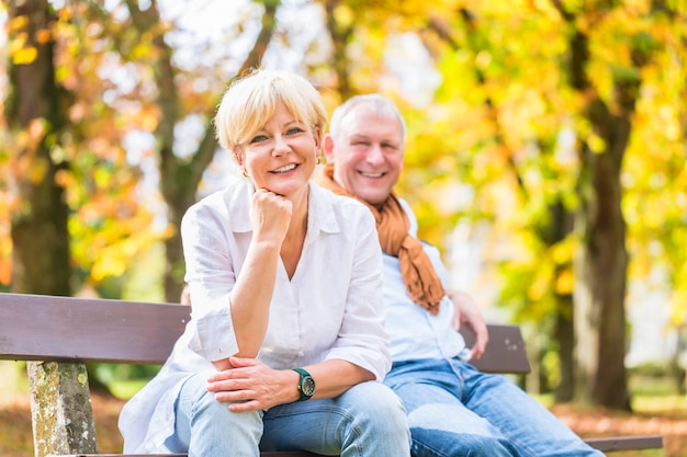 Senior couple sitting on part bench in fall