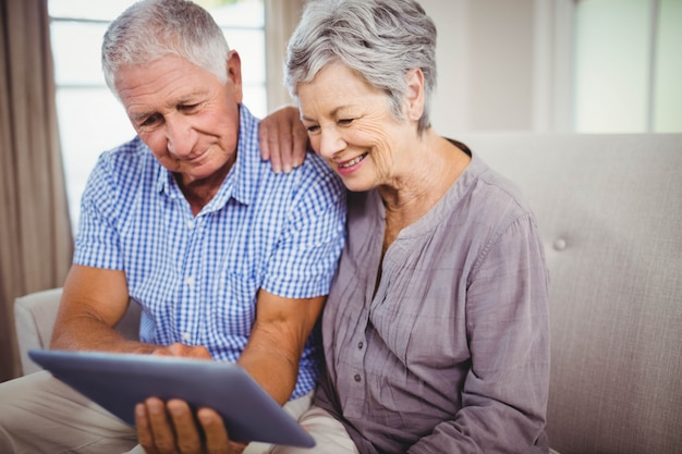 Senior couple sitting on sofa and looking at digital tablet in living room