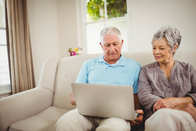 Senior couple sitting on sofa and looking at laptop in living room