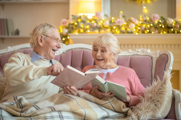 Senior couple sitting on a sofa and reading books