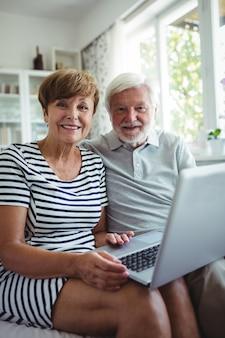 Senior couple sitting on sofa with a laptop