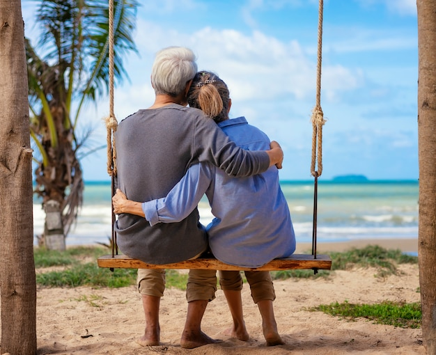 Senior couple sitting on a swing on the beach