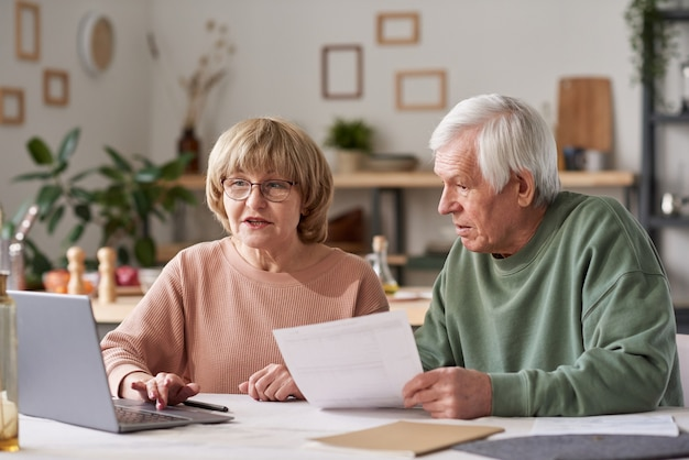 Senior couple sitting at the table and using laptop to pay for bills online in the kitchen