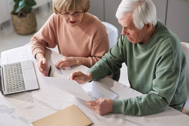 Senior couple sitting at the table with laptop and examining financial documents they paying bills for apartment