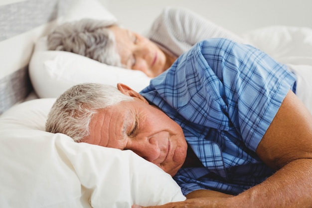 Senior couple sleeping on bed in bedroom