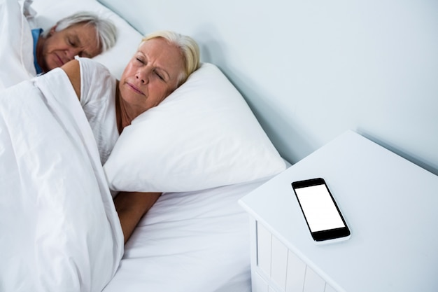 Senior couple sleeping on bed with phone on table