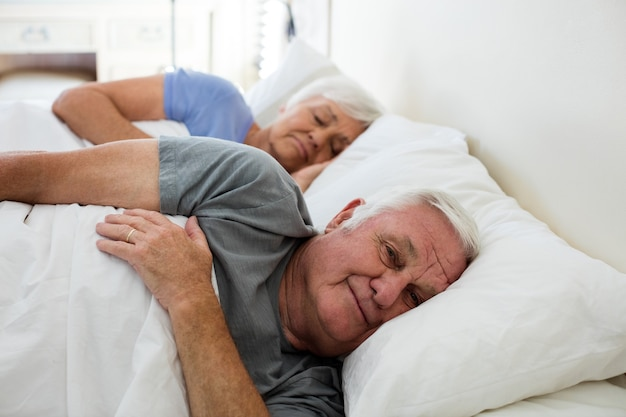 自宅の寝室で寝ている年配のカップル