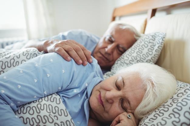 Пожилая пара спит на кровати