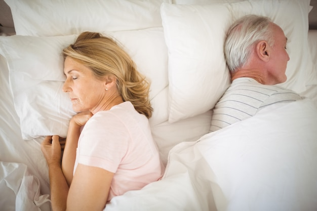 Старшая пара, спящая на кровати