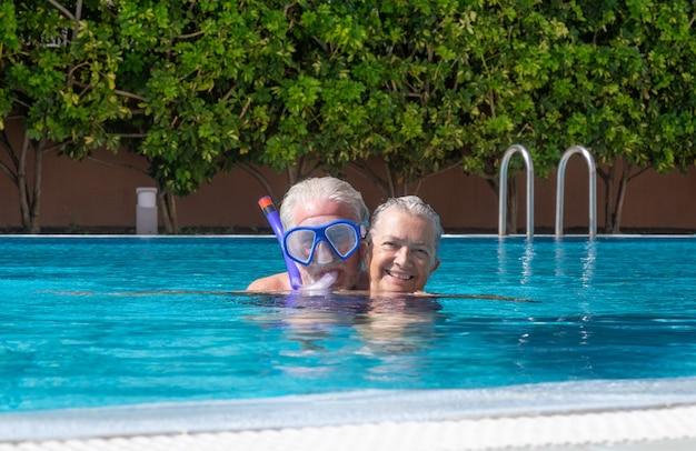 카메라를 보고 수영장에서 수석 부부 미소. 건강한 활동을 하며 여름 휴가를 즐기는 행복한 은퇴한 사람들