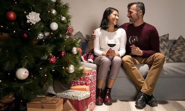 クリスマスツリーの近くでお互いに笑みを浮かべて年配のカップル