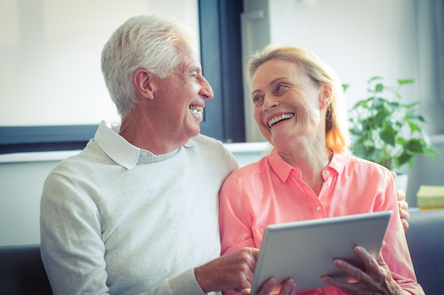 Senior couple smiling while using digital tablet