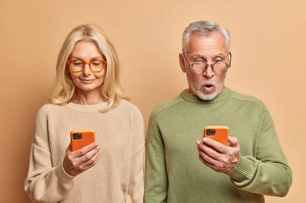 Senior couple stand shoulder to shoulder use smartphones for browsing internet read media website dressed in casual jumpers isolated over brown wall