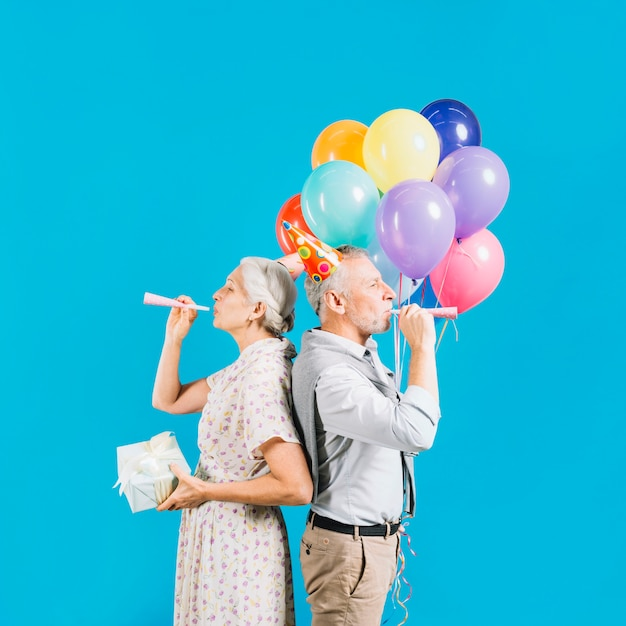 Senior couple standing against each other blowing party horn on blue backdrop