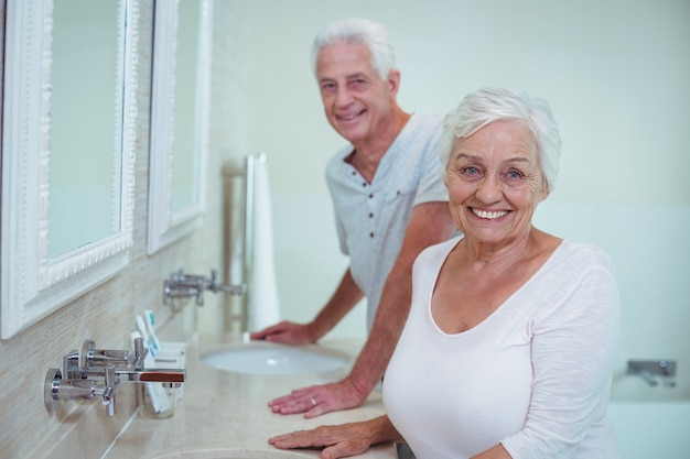 Senior couple standing by mirror in bathroom