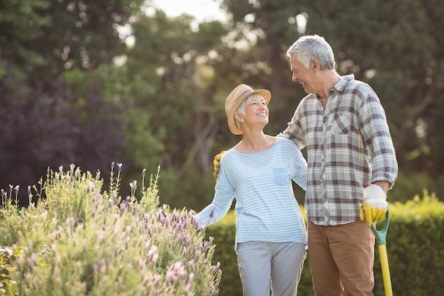 Пожилая пара стоит на заднем дворе