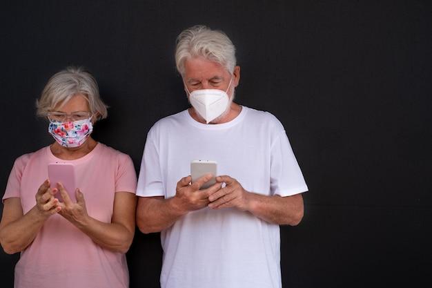 코로나바이러스 때문에 의료용 마스크를 쓰고 스마트폰을 들고 검은 배경에 서 있는 노부부. 전화는 옷의 색상과 결합합니다. 모던함을 즐기는 노년층