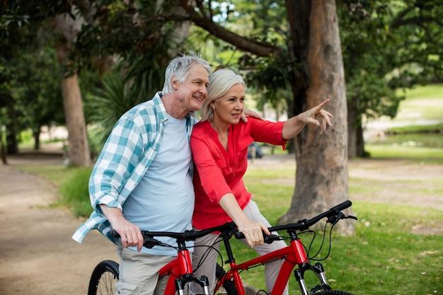 Пожилая пара стоит с велосипедом в парке