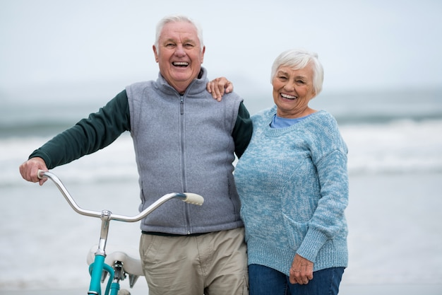 Пожилая пара стоит с велосипедом на пляже