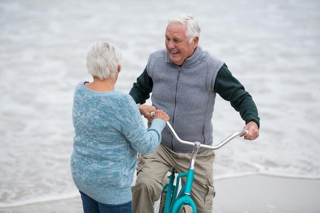 Пожилая пара стоит с велосипедами на пляже