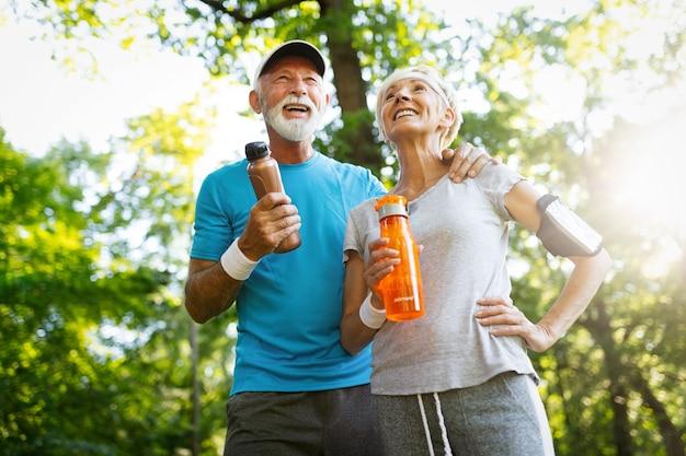 ジョギングをした後も水分補給を続けている年配のカップル
