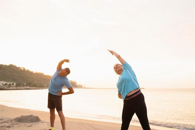 年配のカップルが一緒にビーチでストレッチ
